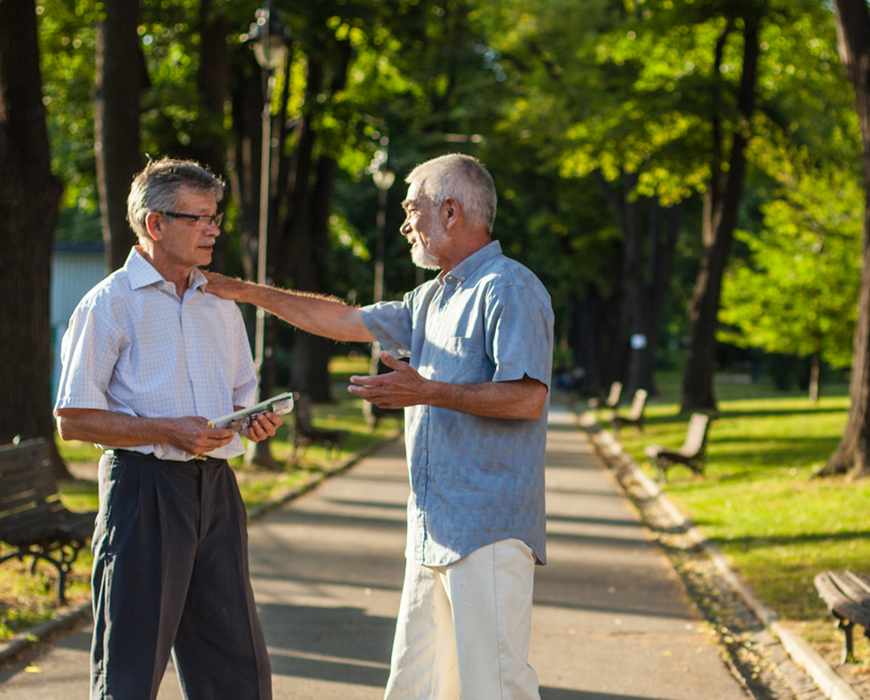 Two elderly men talking about Right of Survivorship in the park with each other. One of the men is grabbing the shoulder of the other while trying to explain something.