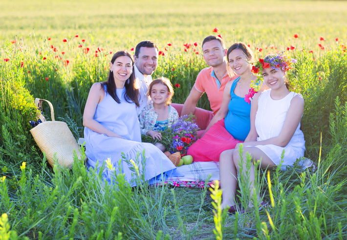is polyamorous relationship marriage legal in canada - polyamorous famiy in a green field with one children and one pregnant woman