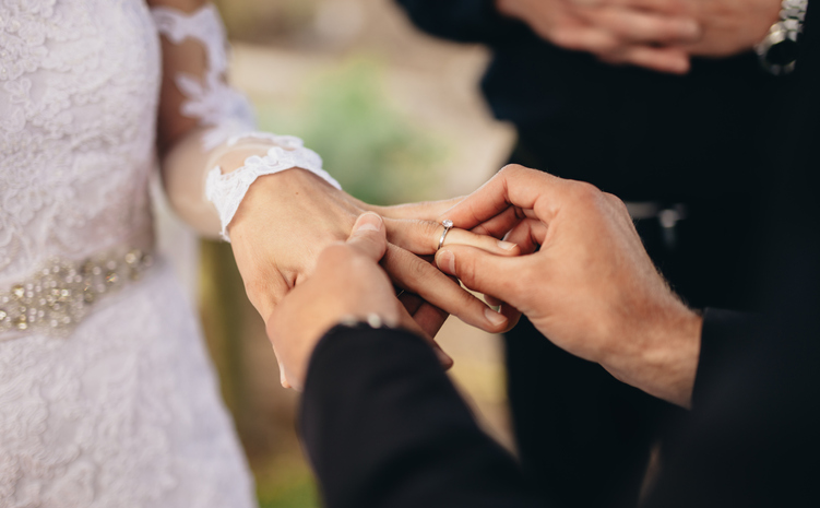 Man placing ring on woman's finger in marriage